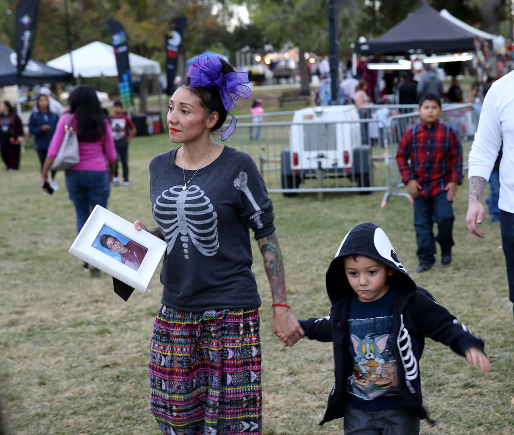 Brenda Occhipinti her son Emiliano, 4, prepare to have a photo of her 12-year-old son Carlo Jr. placed on an altar at the Life in Death: Day of the Dead Festival at Winchester Cultural Center in L ...