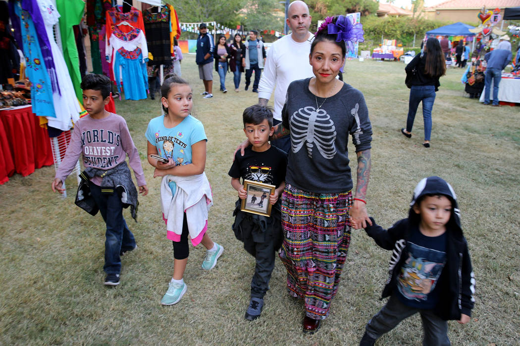 Brenda Occhipinti with her children, from left, Marcelino, 8, Isabella, 11, Santiago, 7, and Emiliano, 4 and their father Carlo Friday, Nov. 2, 2018, with a photo of her 12-year-old son Carlo Jr. ...