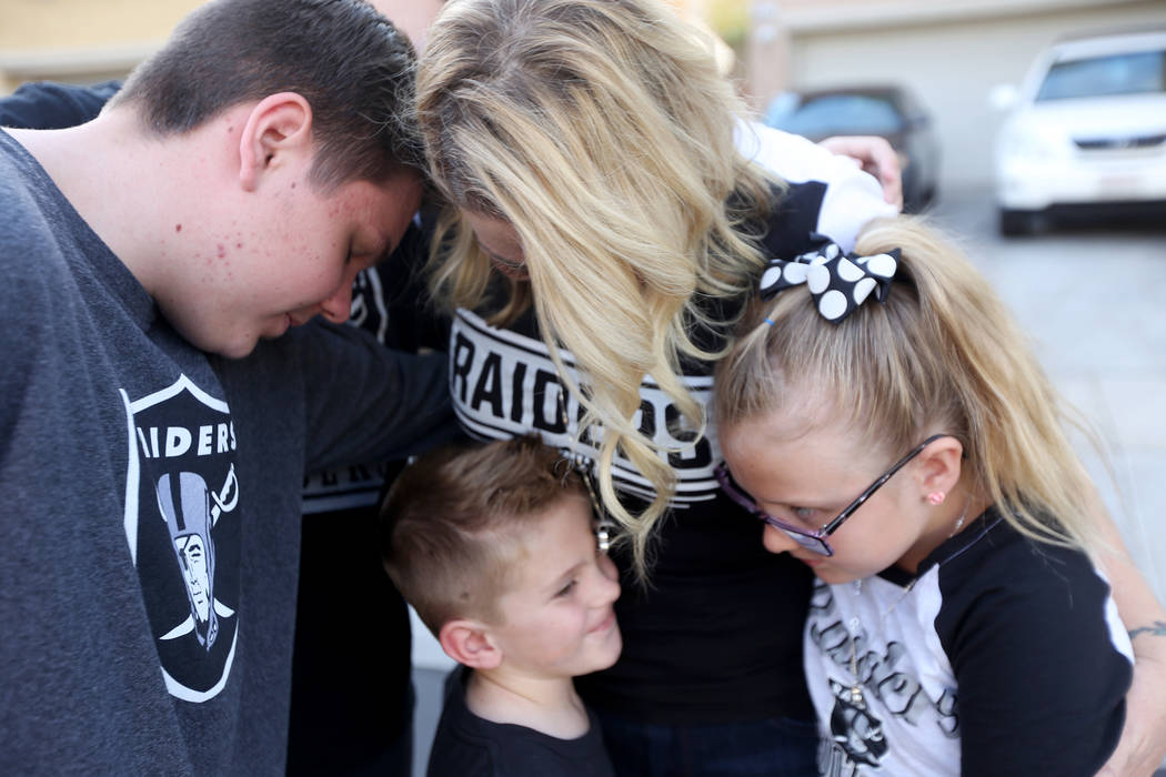The Tracy family, from left, Colin Tracy, 17, Meredith Tracy, Kannon Tracy, 5, and Callie Tracy, 9, embrace after releasing balloons in honor of Russell Tracy's birthday outside their home in Las ...