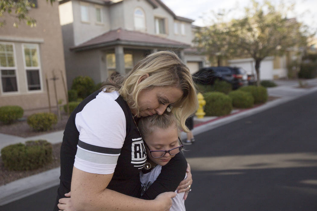 Meredith Tracy embraces her daughter Callie Tracy, 9, after releasing balloons in honor of Russell Tracy's birthday outside their home in Las Vegas, Friday, Nov. 2, 2018. Russell Tracy was killed ...