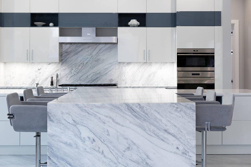 The kitchen features a large marble waterfall-edge island with bar seating. (Steve Morgan)