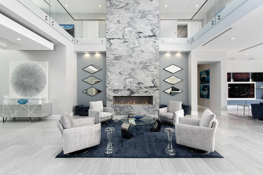 The great room's floor-to-ceiling, gray marble-encased fireplace, framed by a series of diamond-shaped mirrors, serves as a stunning focal point for the main living area. (Steve Morgan)