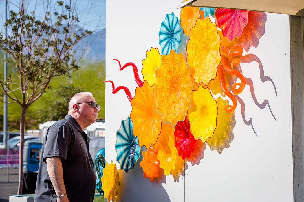 A festival-goer examines a painting at the festival. (Summerlin)