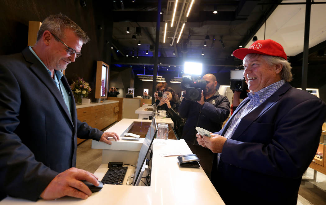 Clark County Commissioner Tick Segerblom, right, is the first customer at Planet 13 Thursday, Nov. 1, 2018. Segerblom is helped by General Manager Mike Poppen. The marijuana store, which bills its ...
