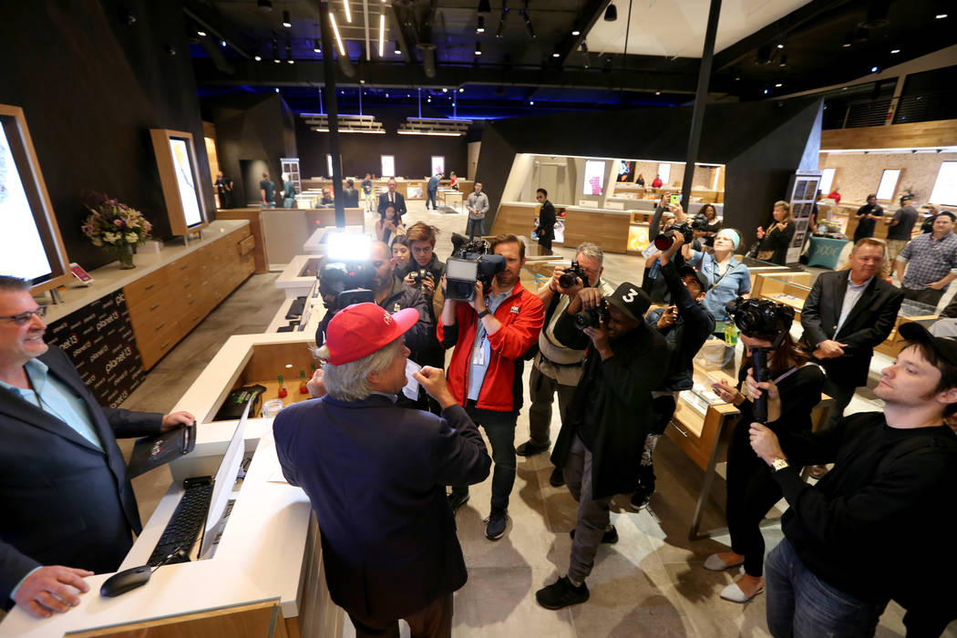Clark County Commissioner Tick Segerblom shows the first purchase at Planet 13 Thursday, Nov. 1, 2018. At left is General Manager Mike Poppen. The marijuana store, which bills itself as one of the ...