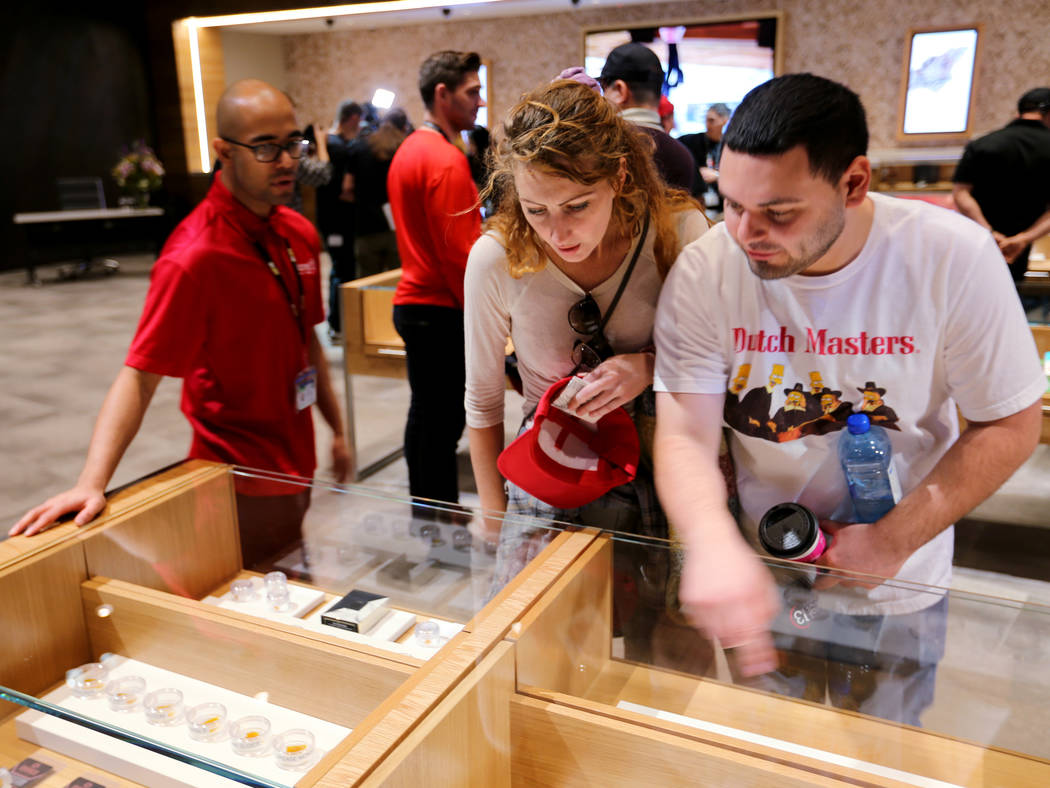 Some of the first customers at Planet 13, which bills itself as one of the largest dispensaries in the world, Kimberly Horan and Michael Pollak, both of Las Vegas, check out product Thursday, Nov. ...