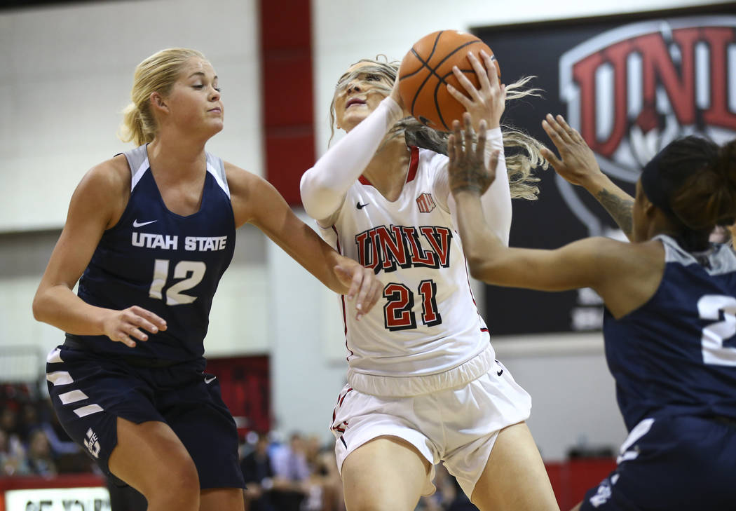 UNLV Lady Rebels forward/center Katie Powell (21) drives as Utah State Aggies guard/forward Hailey Bassett (12) defends during the second half of a basketball game at the Cox Pavilion in Las Vegas ...