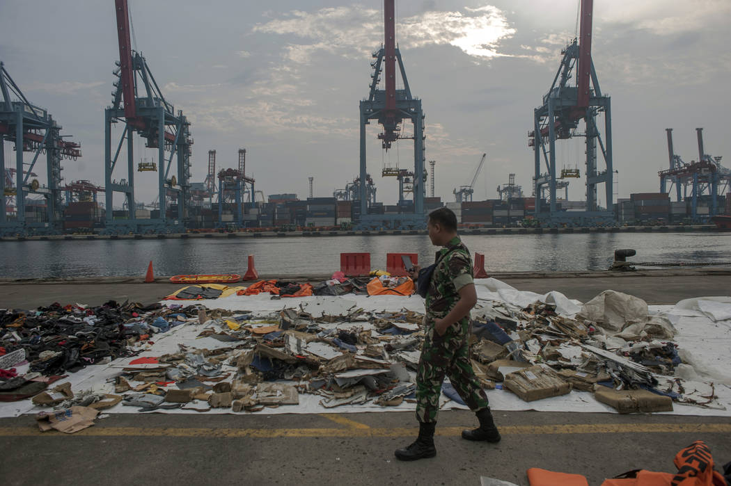 An Indonesian soldiers walk past debris retrieved from the waters where Lion Air flight JT 610 is believed to have crashed at Tanjung Priok Port in Jakarta, Indonesia, Wednesday, Oct. 31, 2018. A ...