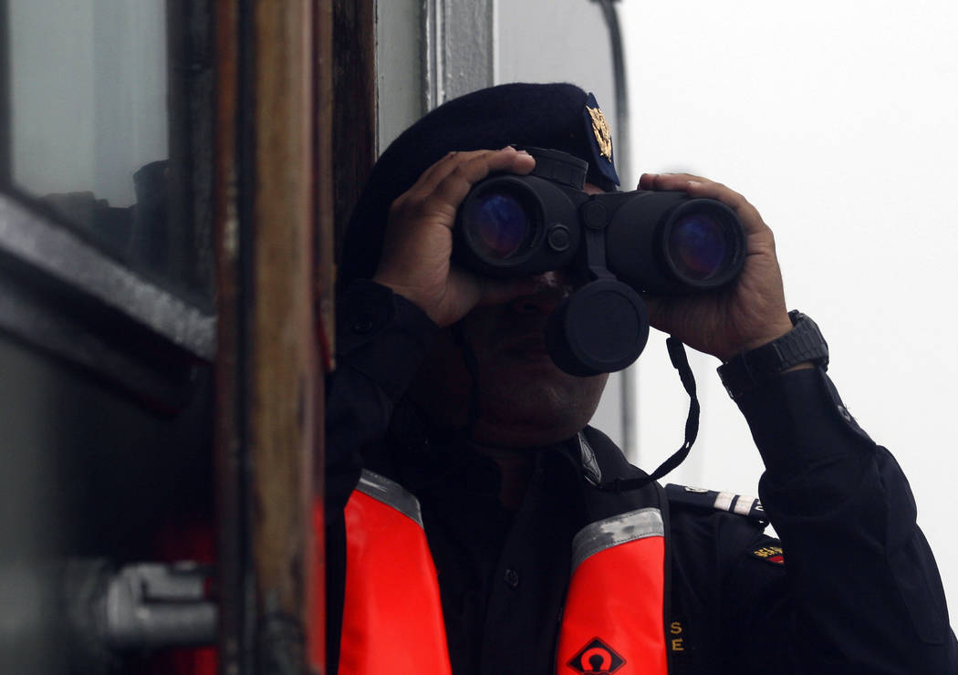 A crew member of a rescue ship uses his binocular during a search operation for the victims of Lion Air plane crash in the waters of Tanjung Karawang, Indonesia, Wednesday, Oct. 31, 2018. A massiv ...
