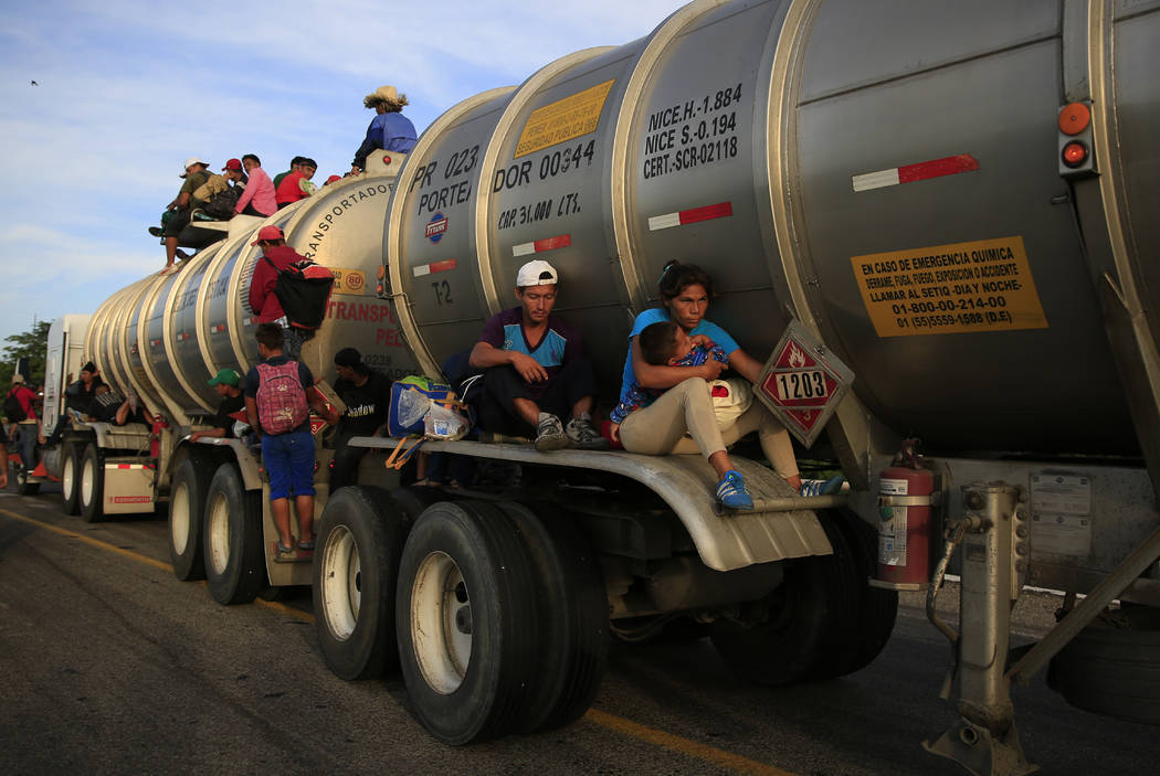 A woman holding her baby hitches a ride on the fender of a tanker in Niltepec, Mexico, Tuesday, Oct. 30, 2018. The caravan of thousands of migrants is continuing its slow advance, setting off thro ...