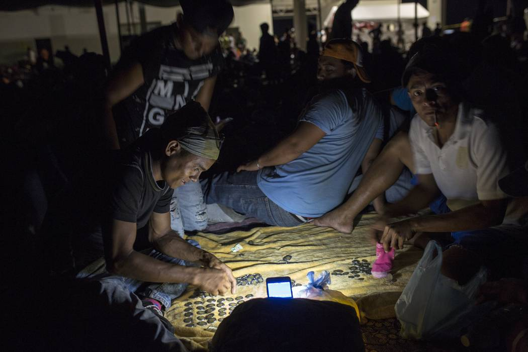 Honduran migrant Nelson Ruiz Madariaga counts coins collected while begging in the street, at a camp set up by a caravan of thousands of Central American migrants in Juchitan, Mexico, Tuesday, Oct ...