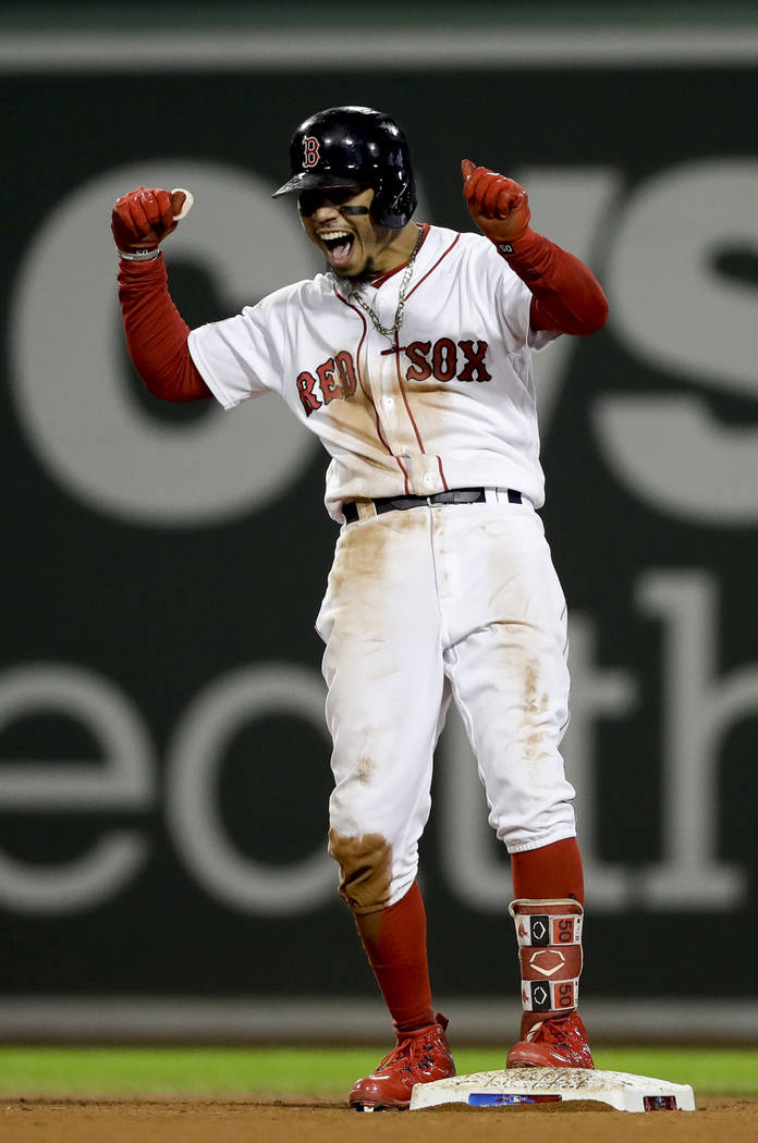 Boston Red Sox's Mookie Betts celebrates after his RBI-double against the Houston Astros during the eighth inning in Game 2 of a baseball American League Championship Series on Sunday, Oct. 14, 20 ...