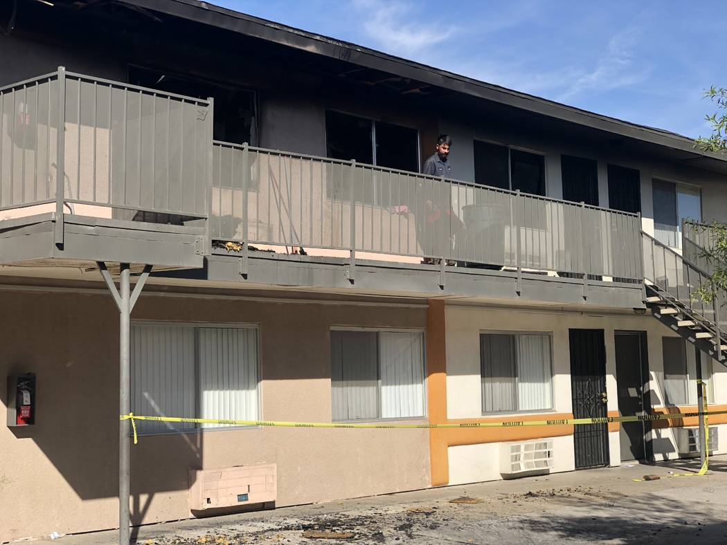 A maintenance worker at Corona Del Sol Apartments cleans up debris after a fatal fire in the east Las Vegas Valley complex on Saturday, Oct. 27, 2018. (Rio Lacanlale/Las Vegas Review-Journal)