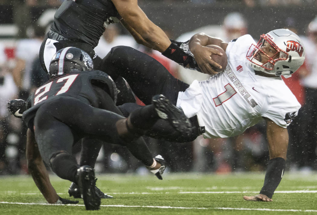 UNLV quarterback Armani Rogers (1) is brought to the ground by Arkansas State linebacker Caleb Bonner (22) and defensive back Demari Medley (27) during an NCAA college football game Saturday, Sept ...