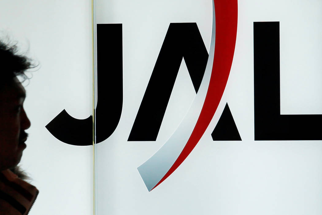 A passenger walks past the Japan Airlines (JAL) logo in 2010 at Haneda Airport in Tokyo, Japan. Japan Airlines co-pilot Katsutoshi Jitsukawa was arrested Sunday after failing a breath test shortly ...