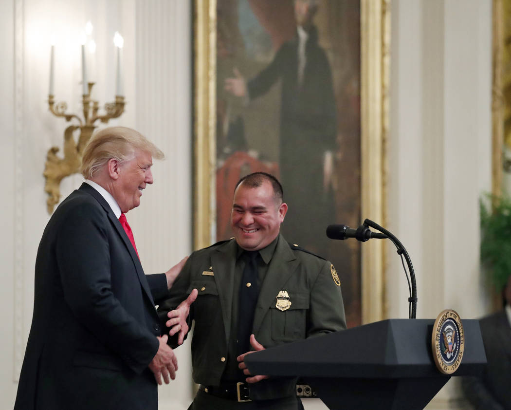 President Donald Trump, left, shakes hands with Customs and Border Patrol agent Adrian Anzaldua, during an event to salute U.S. Immigration and Customs Enforcement (ICE) officers and U.S. Customs ...