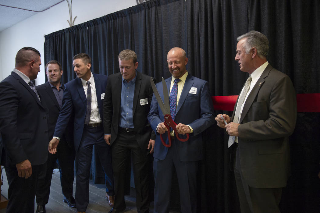 Jeff Iverson, second from right, founder of CrossRoads of Southern Nevada, gets ready for the CrossRoads of Southern Nevada ribbon cutting ceremony at its new facility in Las Vegas, Thursday, Nov. ...
