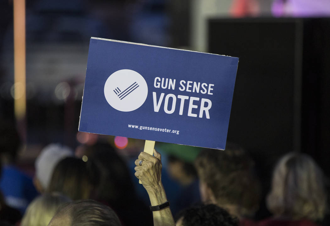 Supporters of new gun control legislation hold up signs during a Get-Out-The-Vote rally on Friday, November 2, 2018, at First Friday, in Las Vegas. Benjamin Hager Las Vegas Review-Journal