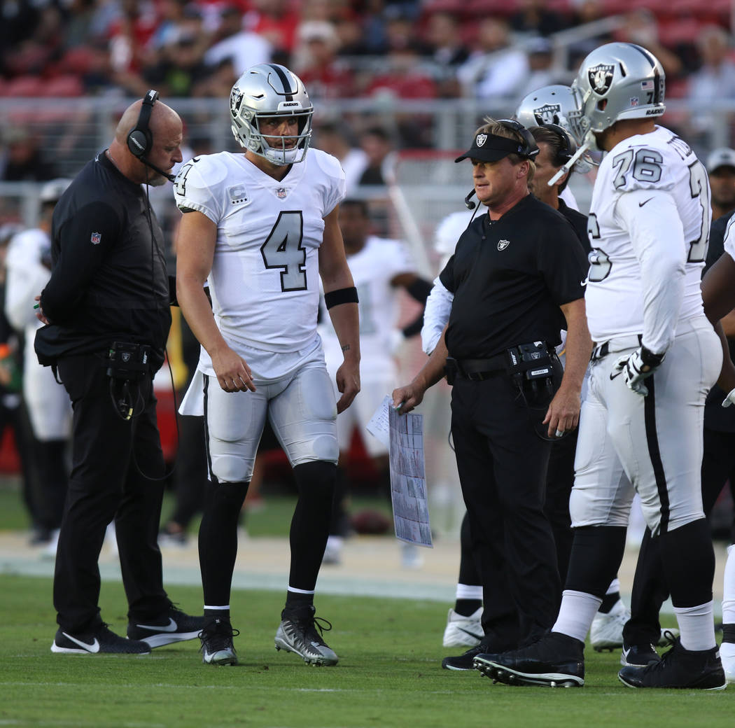 Oakland Raiders offensive coordinator Tom Cable, quarterback Derek Carr (4), head coach Jon Gruden and offensive guard Jon Feliciano (76) look on as Kolton Miller (77), not pictured, lays injured ...