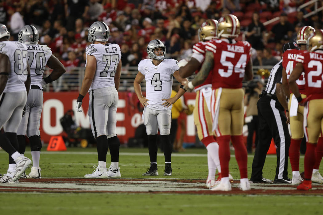Oakland Raiders quarterback Derek Carr (4) looks at a replay where he fell over his own offensive lineman during the first half of their NFL game in Santa Clara, Calif., Thursday, Nov. 1, 2018. He ...