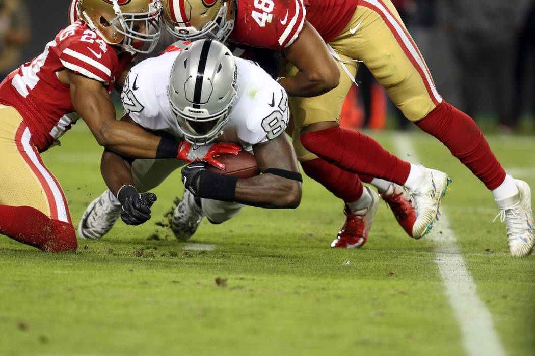 Oakland Raiders tight end Jared Cook (87) holds on to the football as he's tackled by defensive back K'Waun Williams (24) and middle linebacker Fred Warner (48) during the first half of their NFL ...