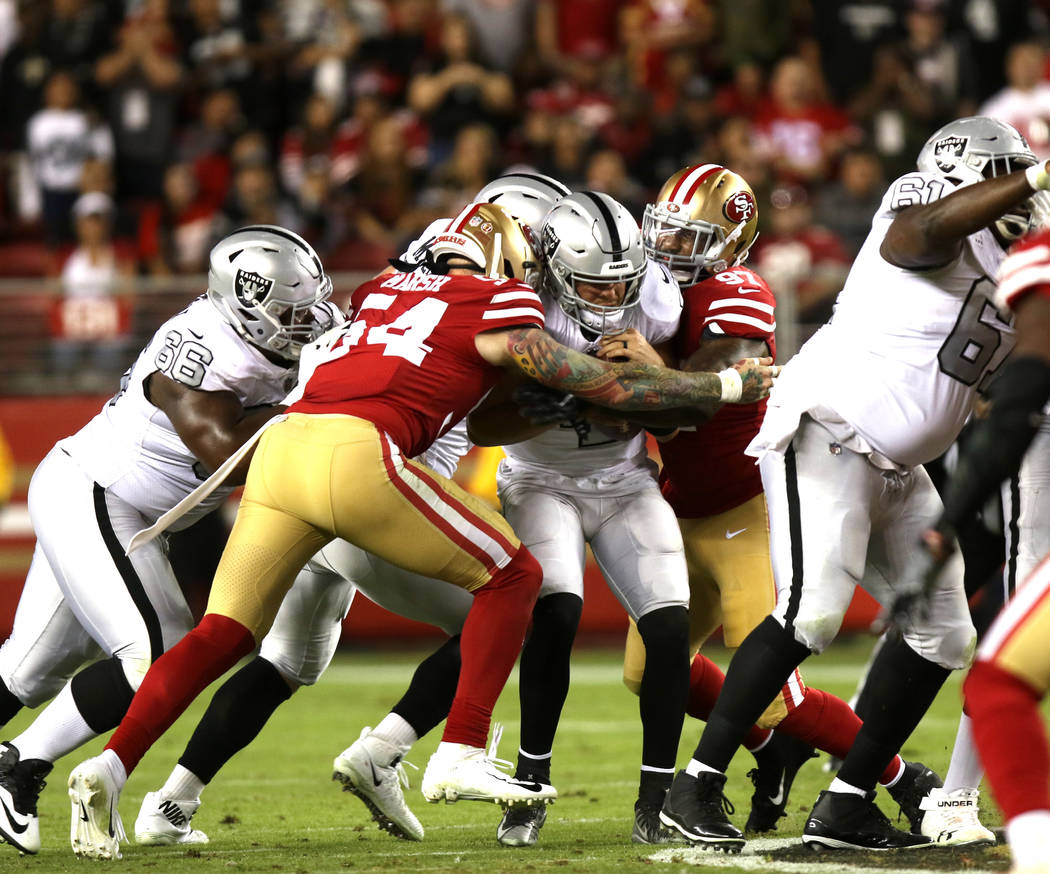 Oakland Raiders quarterback Derek Carr (4) is sacked by San Francisco 49ers defensive end Cassius Marsh (54) and linebacker Dekoda Watson (97) during the first half of their NFL game in Santa Clar ...