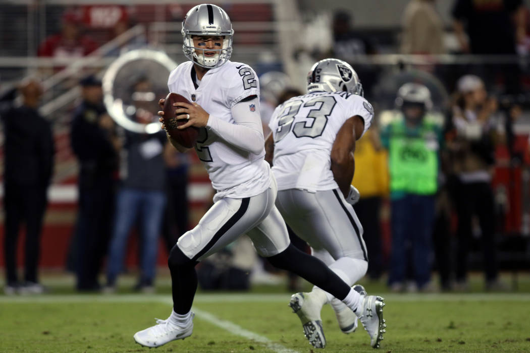 Oakland Raiders quarterback A.J. McCarron (2) rolls out to pass after faking a handoff to running back DeAndre Washington (33) during the second half of their NFL game against the San Francisco 49 ...