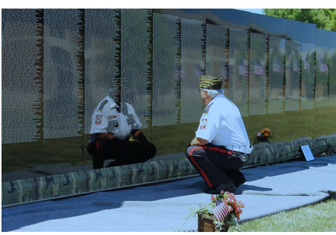 People stand before the names of service men and women etched in The Vietnam Traveling Memorial Wall. Photo courtesy of The Vietnam Traveling Memorial Wall.