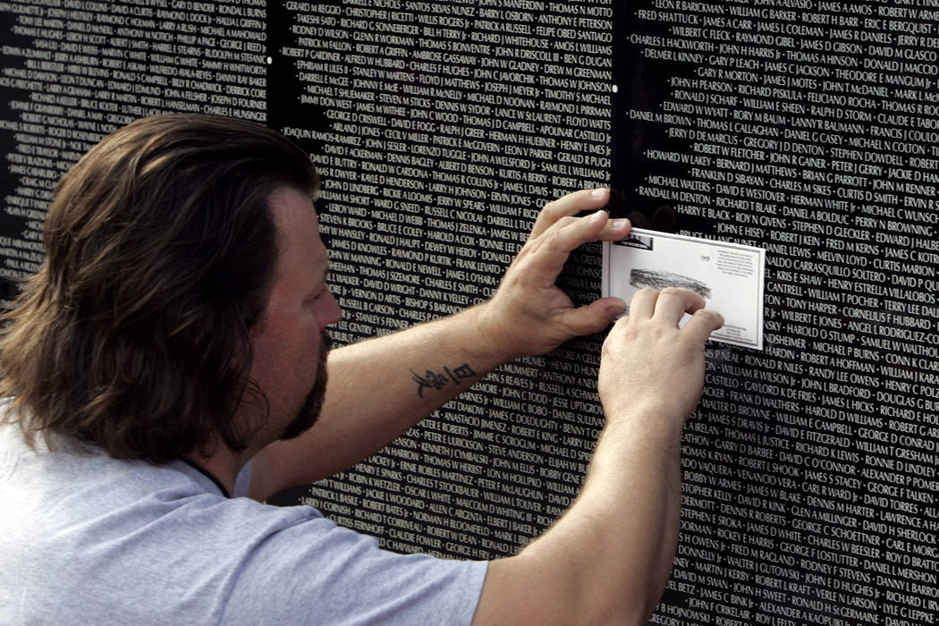 Trace Williford makes a impression of his brother-in-laws name, Frankie Gilchrist who died in 1968 from a land mine at the Moving Wall at Main Street Station parking lot in 2005. (John Gurzinski/L ...