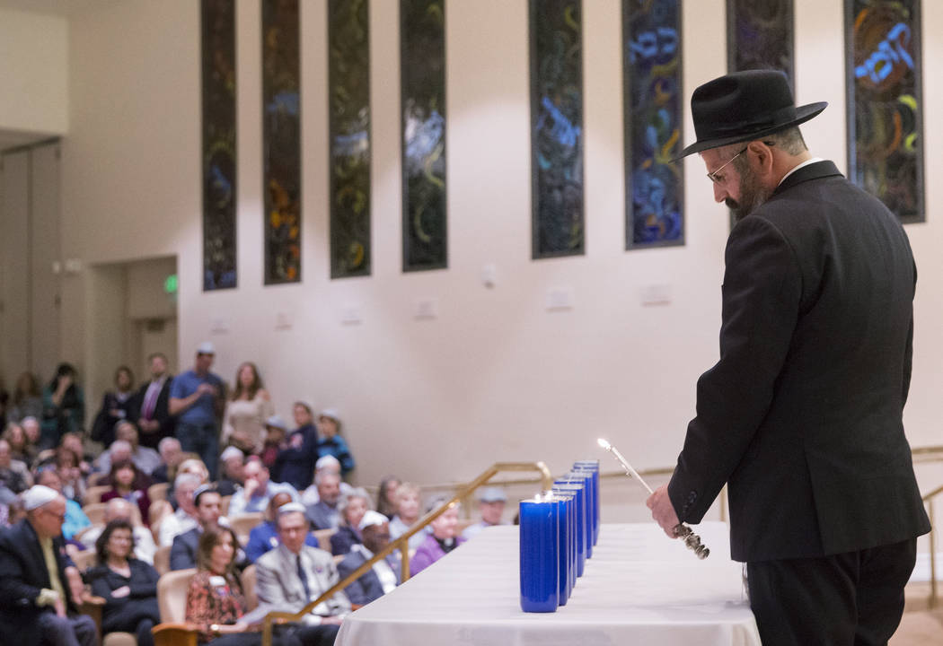 Rabbi Mendy Harlig lights a candle during a vigil on Thursday, November 1, 2018, at Temple Beth Sholom in Las Vegas for the 11 people killed at the Tree of Life synagogue in Pittsburgh, Pa., on Sa ...