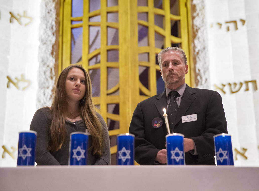 Ken Moskowitz, right, and Ari Goodman light candles during a vigil on Thursday, November 1, 2018, at Temple Beth Sholom in Las Vegas for the 11 people killed at the Tree of Life synagogue in Pitts ...