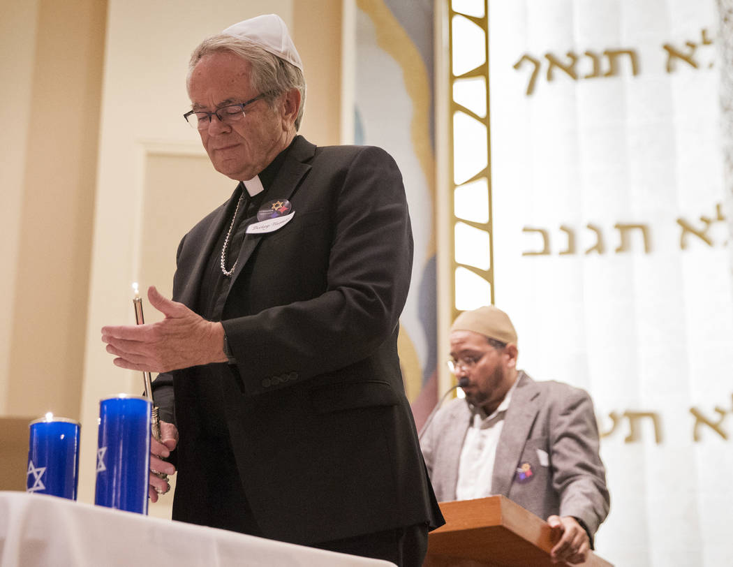Bishop George Leo Thomas lights a candle during a vigil on Thursday, November 1, 2018, at Temple Beth Sholom in Las Vegas for the 11 people killed at the Tree of Life synagogue in Pittsburgh, Pa., ...