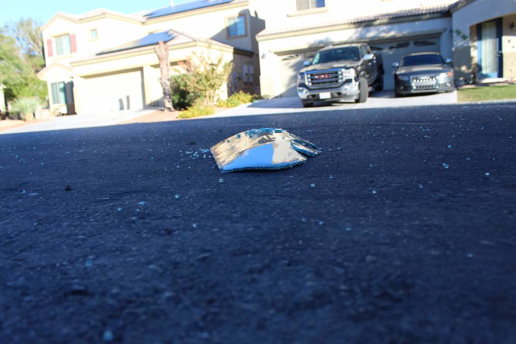 Broken glass is scattered in the street on Friday, Nov. 2, 2018, near a house in the 6700 block of Courtney Michelle Street in North Las Vegas that hit by gunfire, killing an 11-year-old girl on T ...