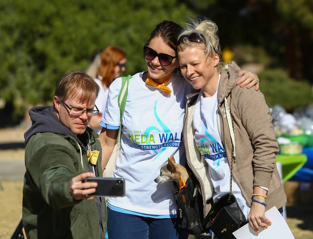 Paul Gordon, left, Lindsey Ricciardi and Allison Reich take a photograph together before the Las Vegas National Eating Disorder Association walk begins at Sunset Park in Las Vegas, Sunday, Nov. 11 ...