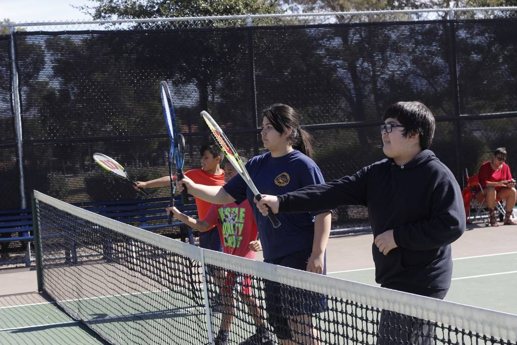 "Students in a tennis class at Craig Ranch Regional Park participate in an exercise, ""Step, lift, punch!,"" to learn how to properly stand during a match and how to hit the ball. (Mia Sims/Las Vegas ..."