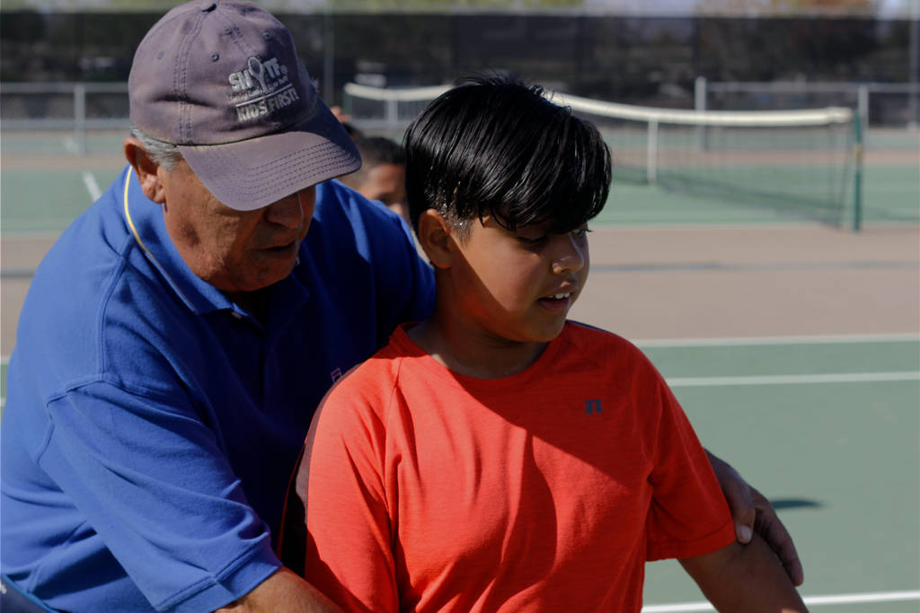 Coach George Cantu helps a student with his stance during tennis lessons at Craig Ranch Regional Park on Saturday. (Mia Sims/Las Vegas Review-Journal @miasims____)