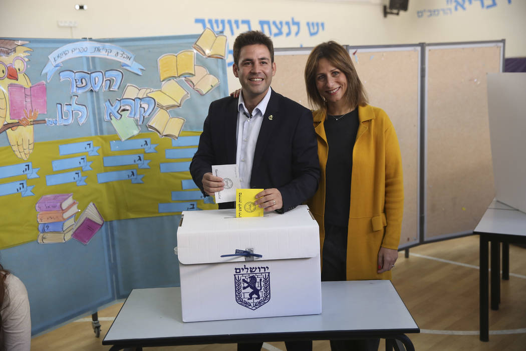 Mayoral candidate Ofer Berkovitch and his wife Dina pose for media as they cast their votes at a polling station during the municipal elections in Jerusalem, Tuesday, Oct. 30, 2018. (AP Photo/Oded ...