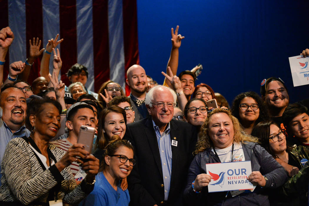 U.S. Sen. Bernie Sanders poses for a photograph with people gathered at the Las Vegas Academy of the Arts as he continues his nine-state swing this week to help boost progressive candidates up and ...