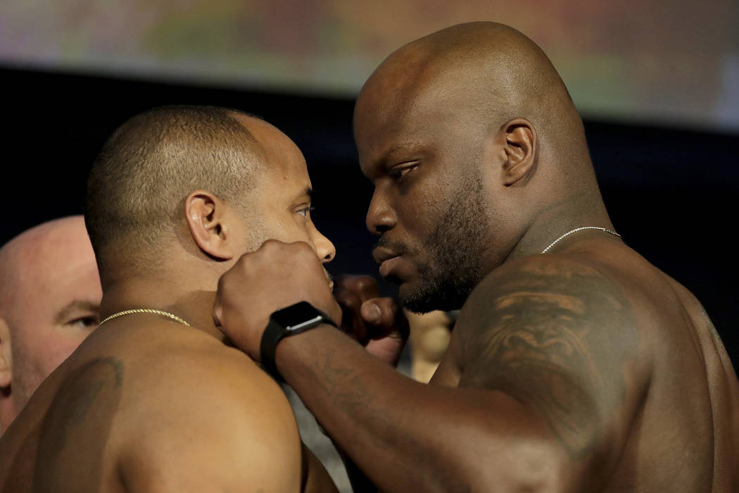 Daniel Cormier, left, and Derrick Lewis square off for photographers during the weigh-ins for their heavyweight mixed martial arts bout at UFC 230, Friday, Nov. 2, 2018, at Madison Square Garden i ...
