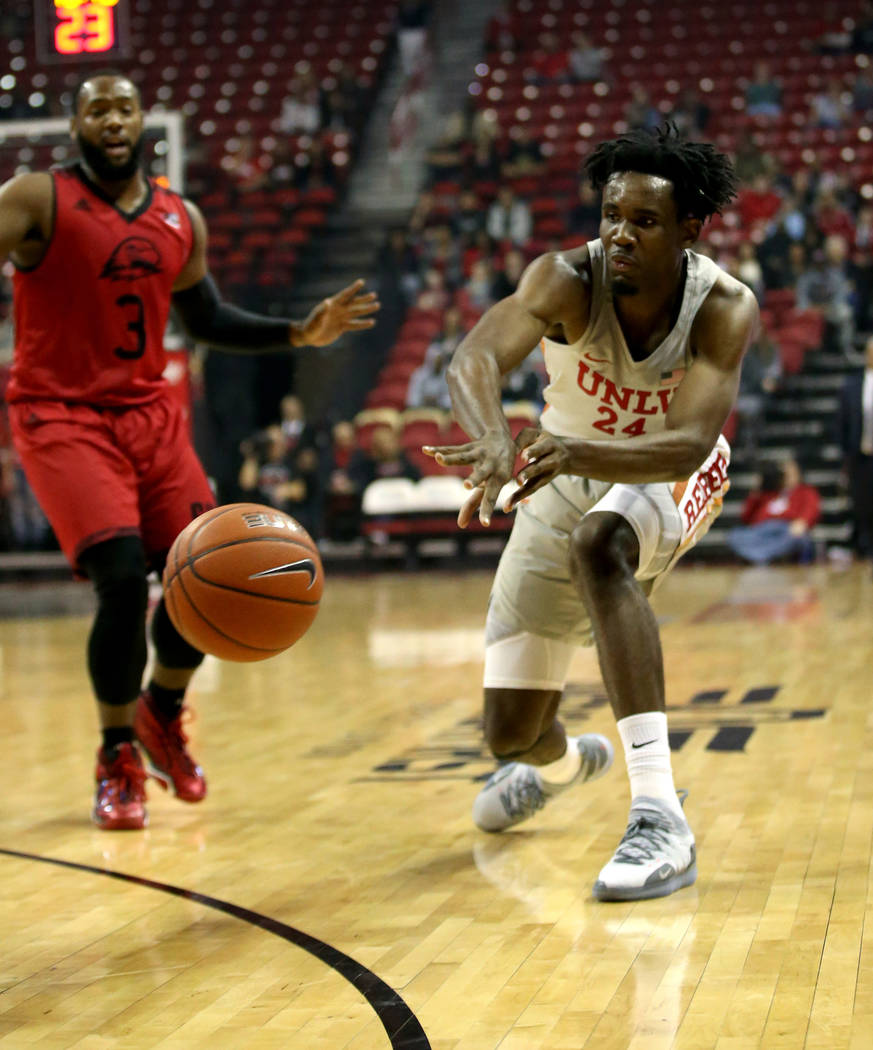 UNLV Rebels forward Joel Ntambwe (24) passes in front of Southern Utah Thunderbirds guard Dre Marin (4) in the first half of their NCAA basketball game at the Thomas & Mack Center in Las Vegas ...