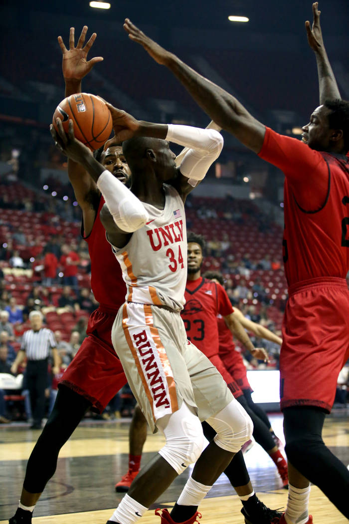 UNLV Rebels forward Cheikh Mbacke Diong (34) is trapped by Southern Utah Thunderbirds forward Andre Adams (32), left, and Southern Utah Thunderbirds forward Dwayne Morgan (25) in the first half of ...