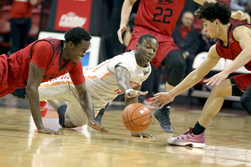 UNLV Rebels forward Cheickna Dembele (15) dives for a loose ball between Southern Utah Thunderbirds forward Dwayne Morgan (25), left, and guard Dre Marin (4) in the first half of their NCAA basket ...
