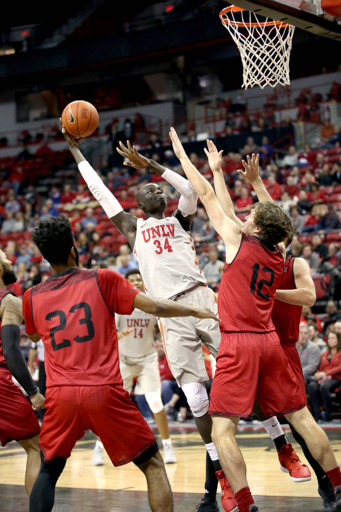 UNLV Rebels forward Cheikh Mbacke Diong (34) shoots between Southern Utah Thunderbirds guard Cameron Oluyitan (23) and Southern Utah Thunderbirds forward Maizen Fausett (12) in the second half of ...
