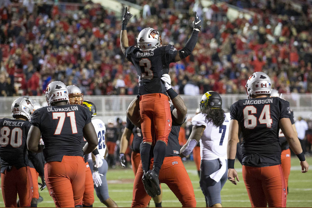 UNLV Rebels running back Lexington Thomas (3) celebrates with teammates after scoring a touchdown against the Nevada Wolf Pack during the first half of an NCAA football game at Sam Boyd Stadium in ...