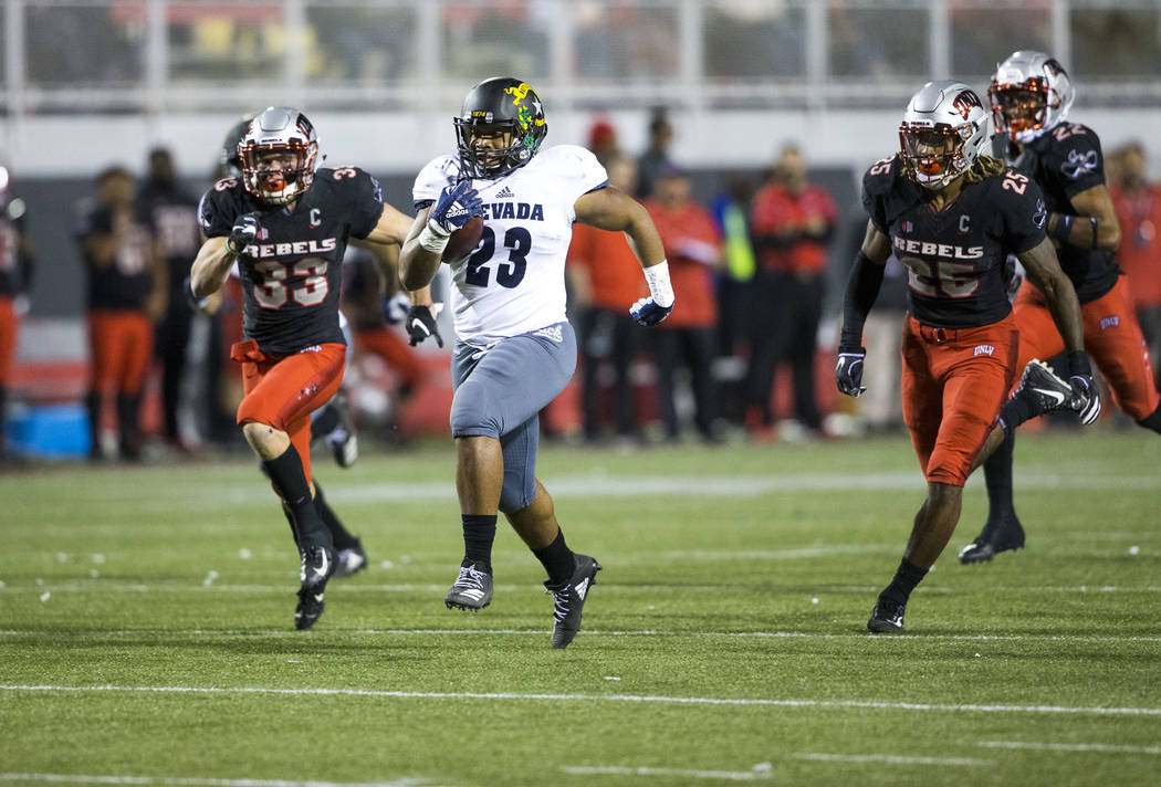 Nevada Wolf Pack running back Kelton Moore (23) breaks past UNLV Rebels defenders for a touchdown during the first half of a NCAA football game at Sam Boyd Stadium in Las Vegas on Saturday, Nov. 2 ...