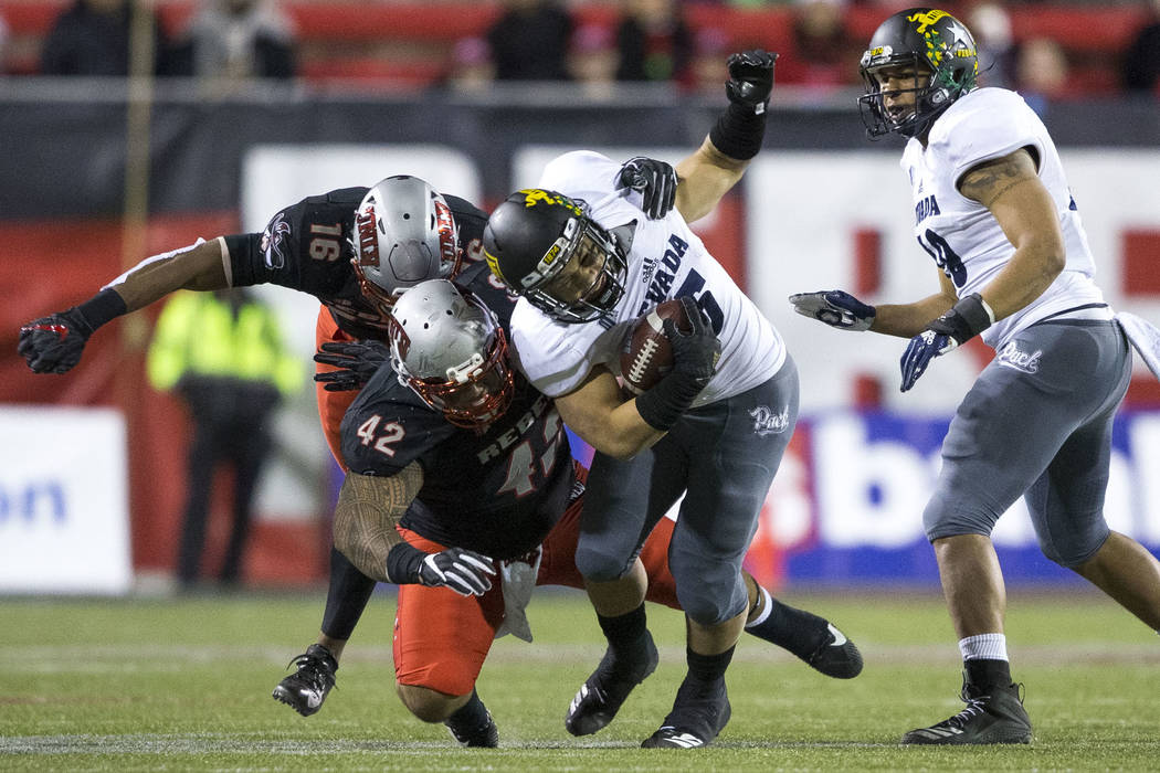 Nevada Wolf Pack running back Toa Taua (35), center, is tackled by UNLV Rebels defensive lineman Salanoa-Alo Wily (42) during the second half of an NCAA football game at Sam Boyd Stadium in Las Ve ...