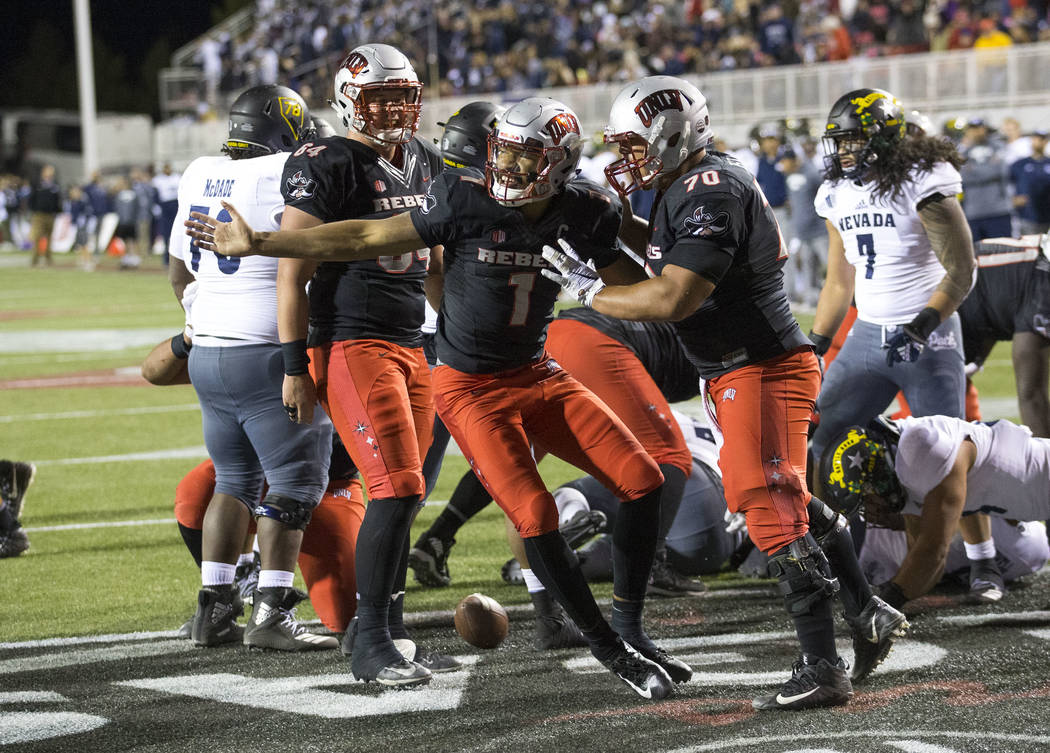UNLV Rebels quarterback Armani Rogers (1), center, celebrates with offensive lineman Sid Acosta (70) after scoring a touchdown against Nevada Wolf Pack during the second half of an NCAA football g ...