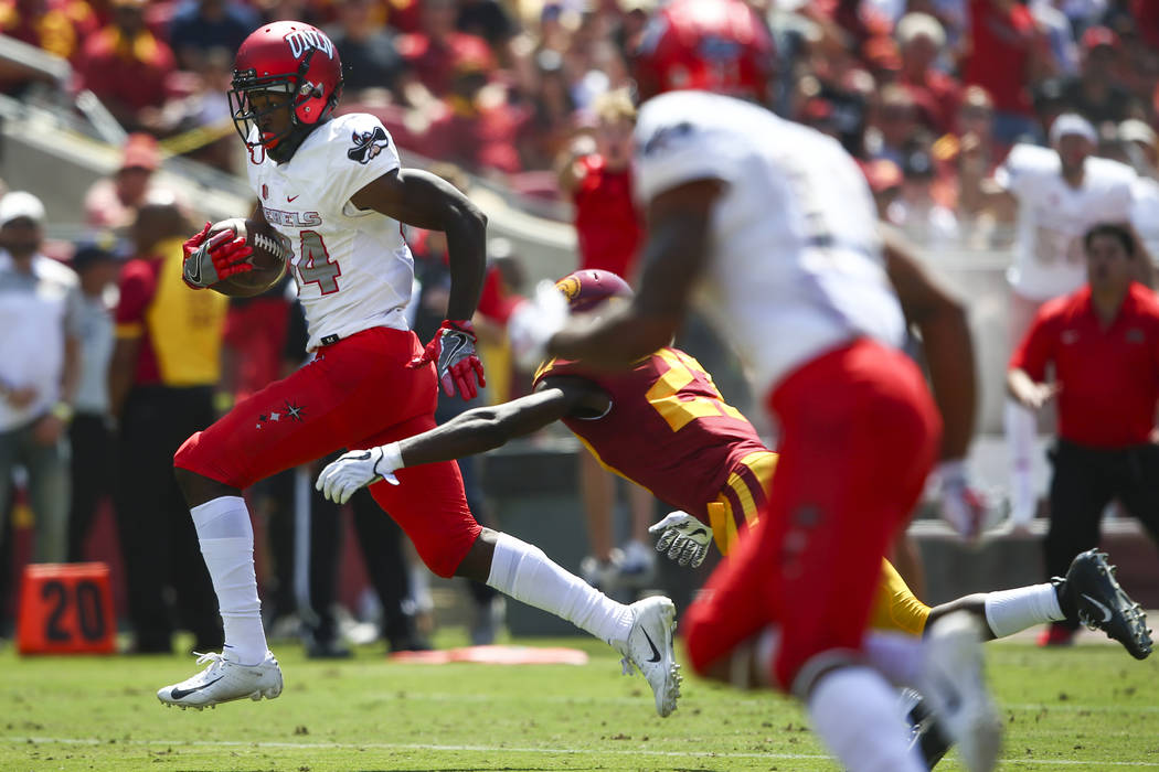 UNLV Rebels wide receiver Kendal Keys (84) avoids a tackle from USC Trojans cornerback Ajene Harris (27) on his way to score a touchdown during the first half of a football game at the Los Angeles ...