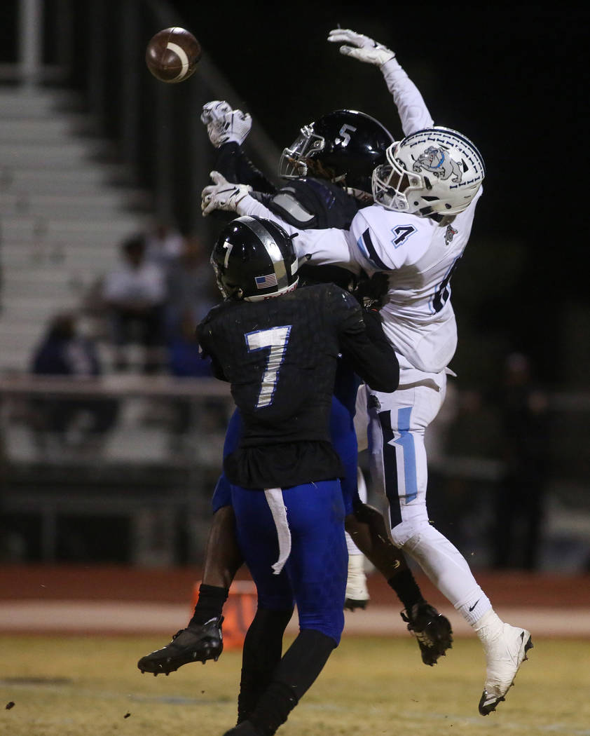 Desert Pines High School's Darius Stewart (5) jumps up for the football while being covered by Centennial High School's Mark Garcia (7) as Desert Pines High School's Darrien Stewart (7) trails be ...