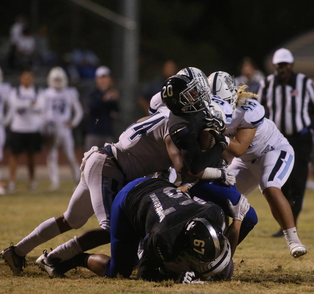 Desert Pines High School's DeAvonte McGee (20) gets tackled by Centennial High School's Atoa Pili-eskeets (14) during the first half of a varsity playoff football game at Desert Pines High School ...